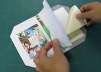 表紙をめくって、芯に貼ってある黄色い両面テープをはがします。表紙用紙はストッパーで固定されているので、位置通りに貼ることができます。