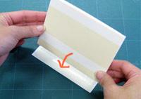 見返し用紙ではさんだ本文の背側をワンタッチテープに押し付けます。
